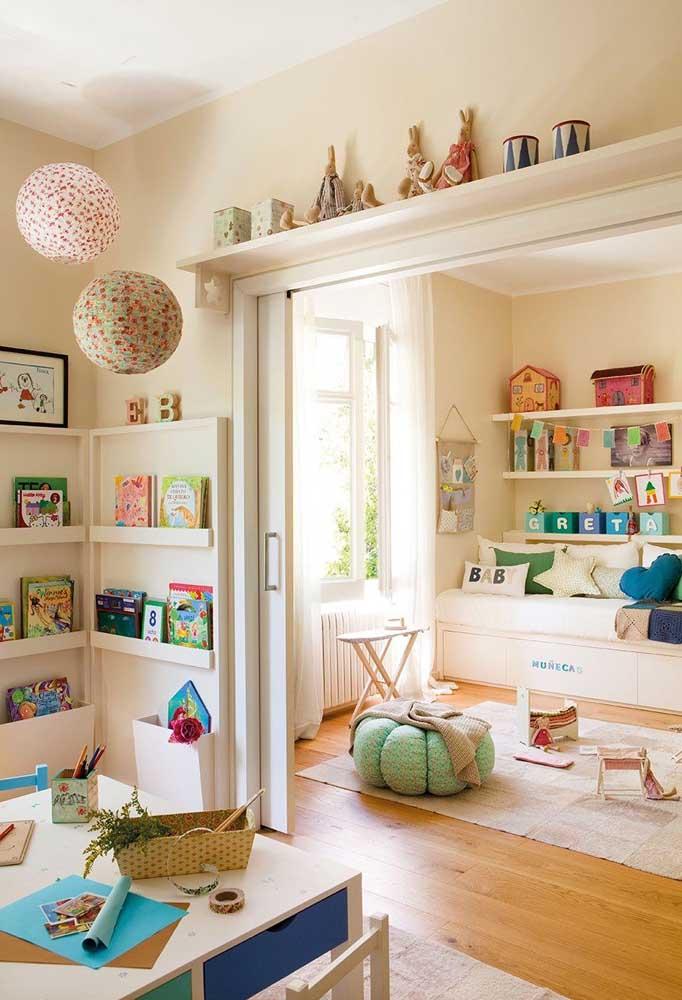 Entre todas as prateleiras que decoram esse quarto infantil, a que mais se destaca é a que fica sobre a porta, exibindo lindos objetos decorativos