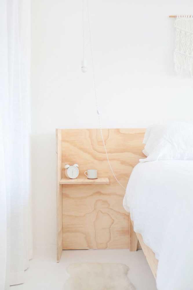 A madeira clara da prateleira forma um bonito contraste no quarto todo branco