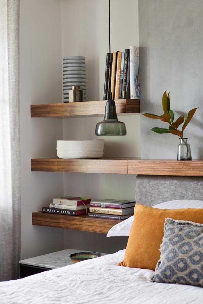 As prateleiras grossas de madeira para o quarto do casal acomodam com beleza e muita organização livros e pequenos objetos decorativos