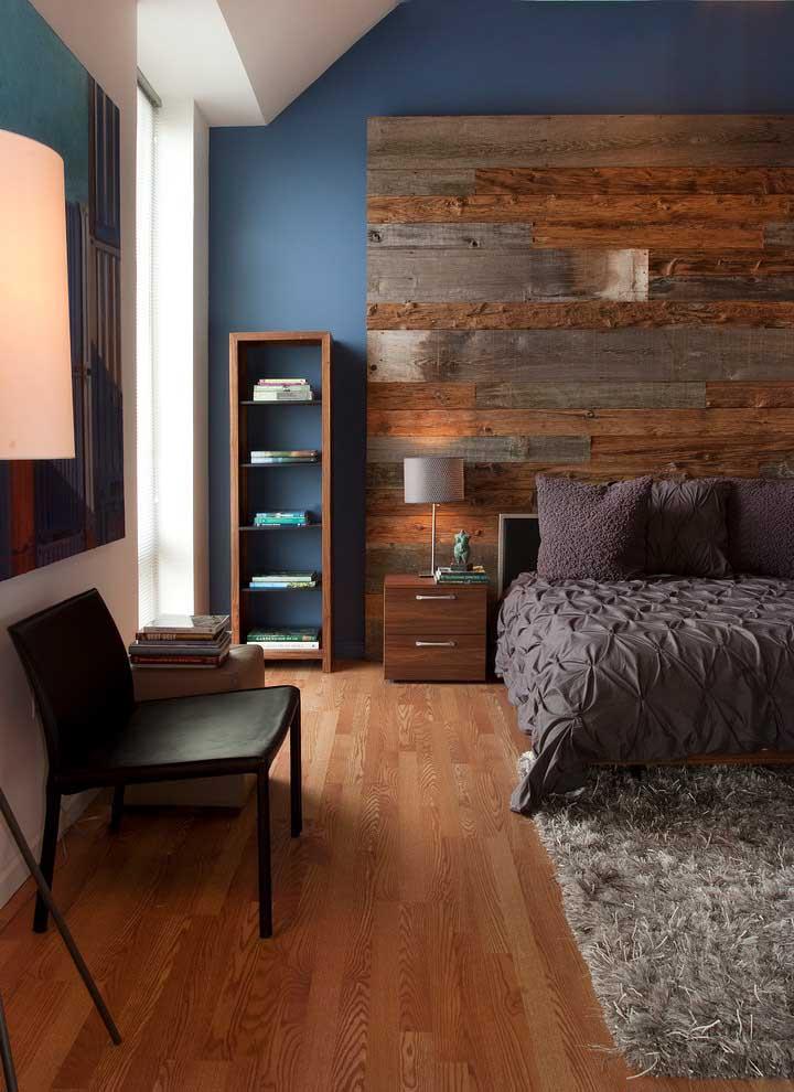 O quarto com cabeceira rústica apostou em uma pequena estante de prateleiras em madeira para combinar