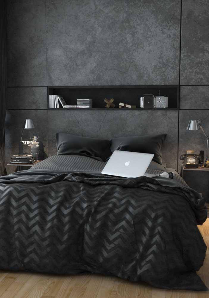 O quarto de tons sóbrios e escuros traz uma prateleira embutida preta sobre a cabeceira