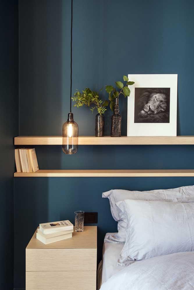 A parede azul petróleo ganhou destaque com as prateleiras de madeira clara