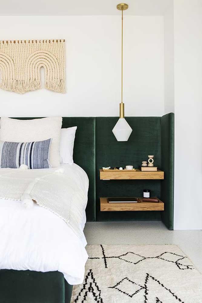 A linda cabeceira de veludo verde desse quarto ganhou a companhia inusitada de duas prateleiras de madeira