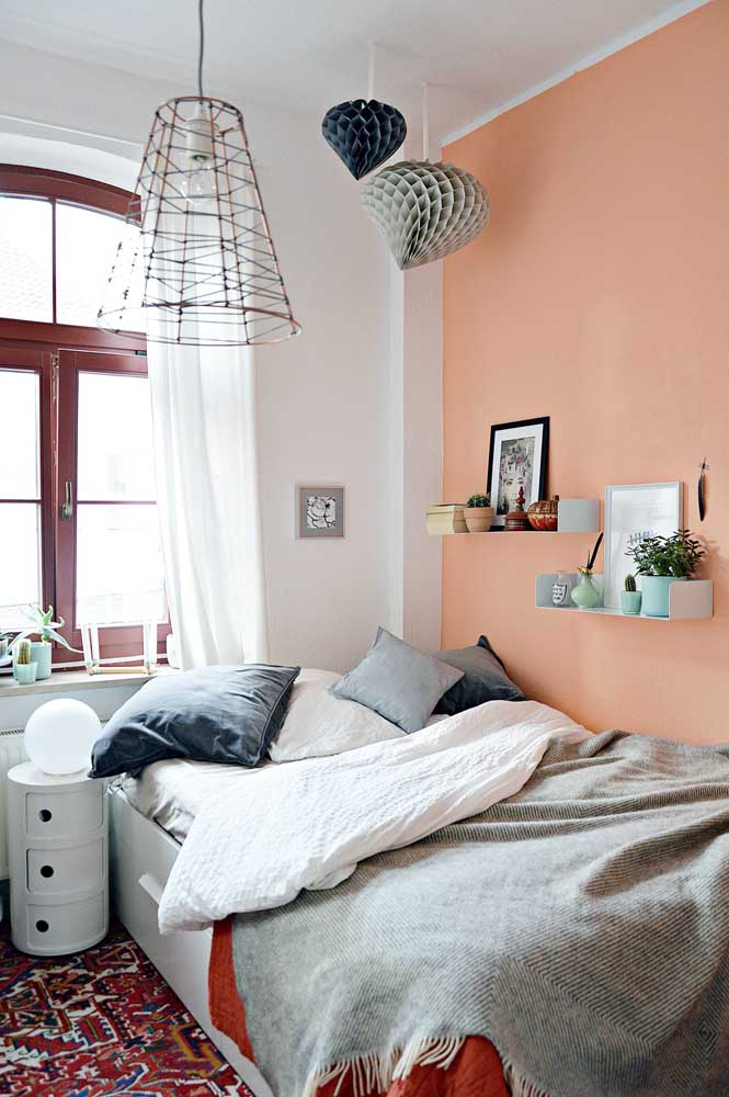 A cama encostada na parede tirou proveito das prateleiras que completam a decoração e a funcionalidade do quarto
