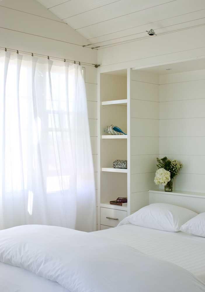 O quarto de casal delicado e romântico traz prateleiras embutidas na parede