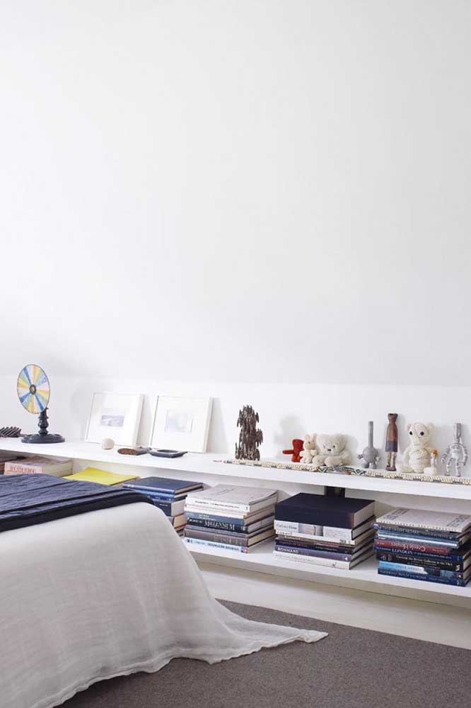 Já essa prateleira instalada rente ao chão traz livros e peças decorativas muito bem organizadas