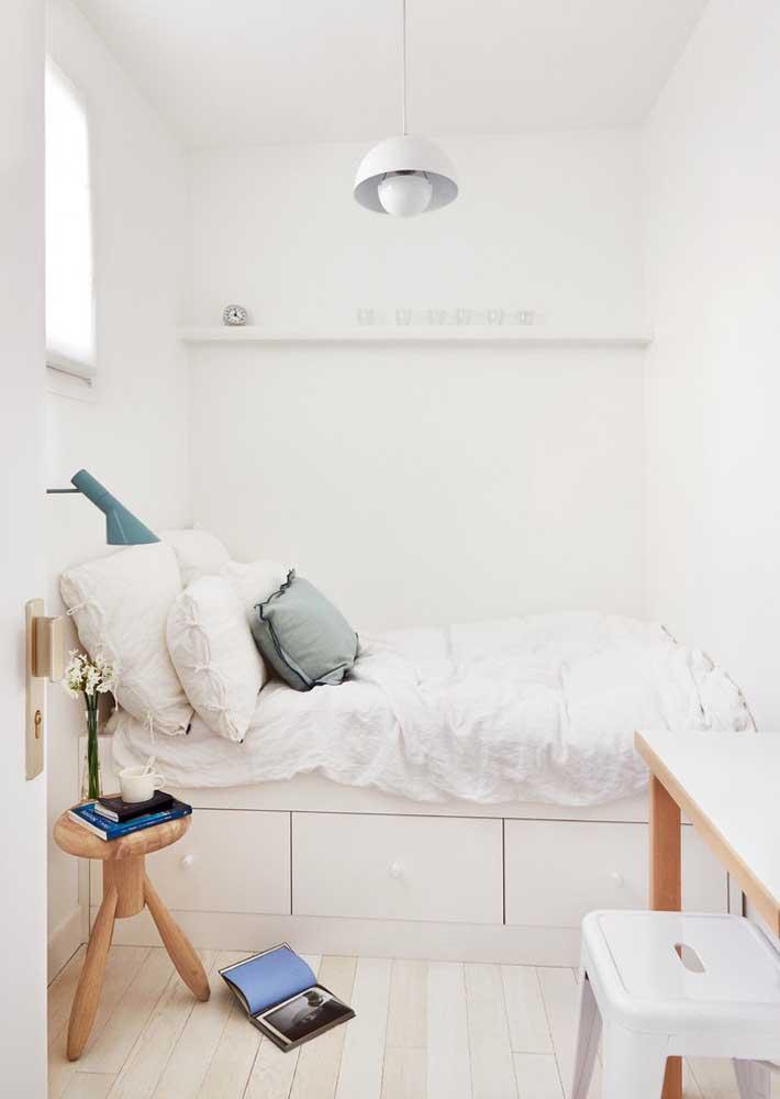 O quarto clean e iluminado traz uma prateleira decorativa acima da cama