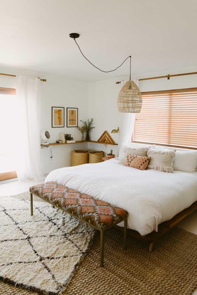 O quarto de estilo boho trouxe uma prateleira de madeira de canto para acomodar objetos decorativos