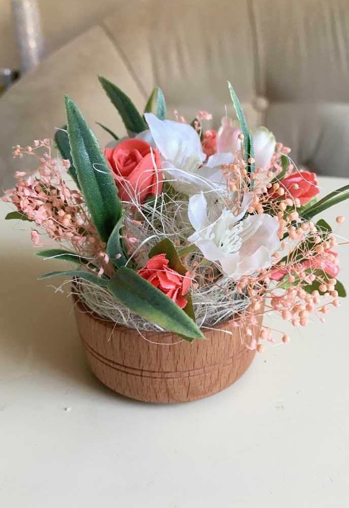 Flores em tecido e folhas de plástico unidas para formar o arranjo perfeito