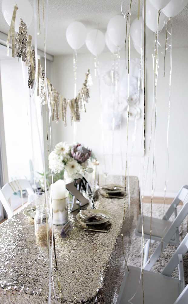 Aqui, outra sala de jantar, só que dessa vez a decoração inclui uma toalha de mesa com paetês prateados