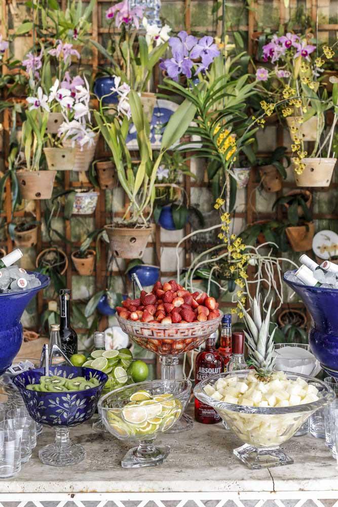 Misture plantas, arranjos de flores e muitas frutas na mesa da ceia de ano novo.