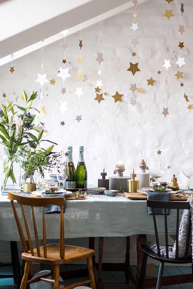 Pendure estrelinhas brilhantes em cima da mesa da ceia de ano novo.