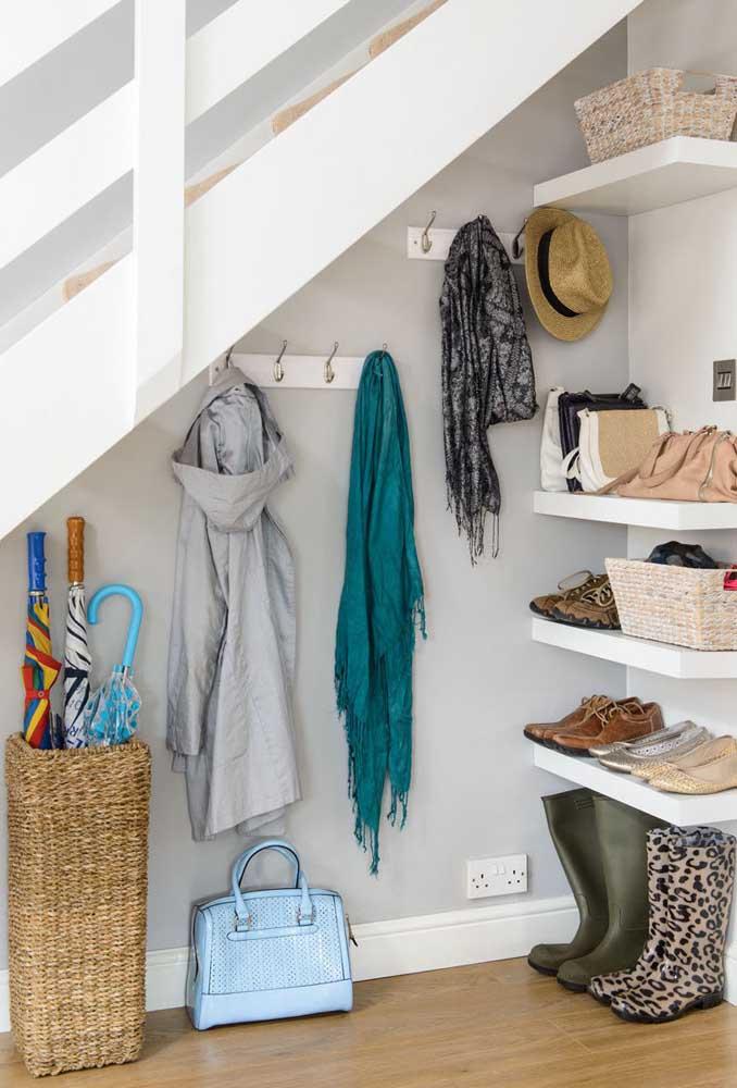 O que acha de colocar prateleiras para organizar suas coisas embaixo da escada?