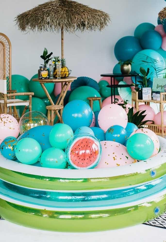 Encha uma piscina de plástico com vários balões personalizados.