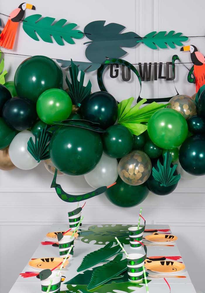 Balões em diferentes tons de verde e enfeites de papel para quem deseja fazer uma festa safári simples, bonita e barata