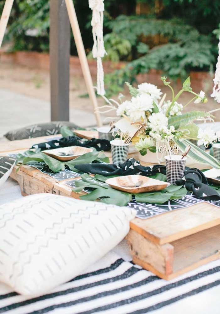 """Festa safári descontraída com todo mundo sentando no chão; repare que a """"mesa"""" foi feita com pallets"""