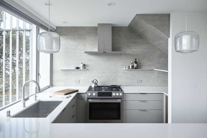 Que tal fazer uma decoração com parede de cimento cru e móveis brancos?