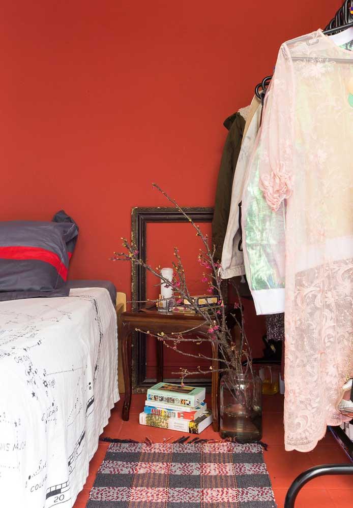 Roupas de cama, tapete e até um vaso com flores são perfeitos para inserir a cor vermelha na decoração.