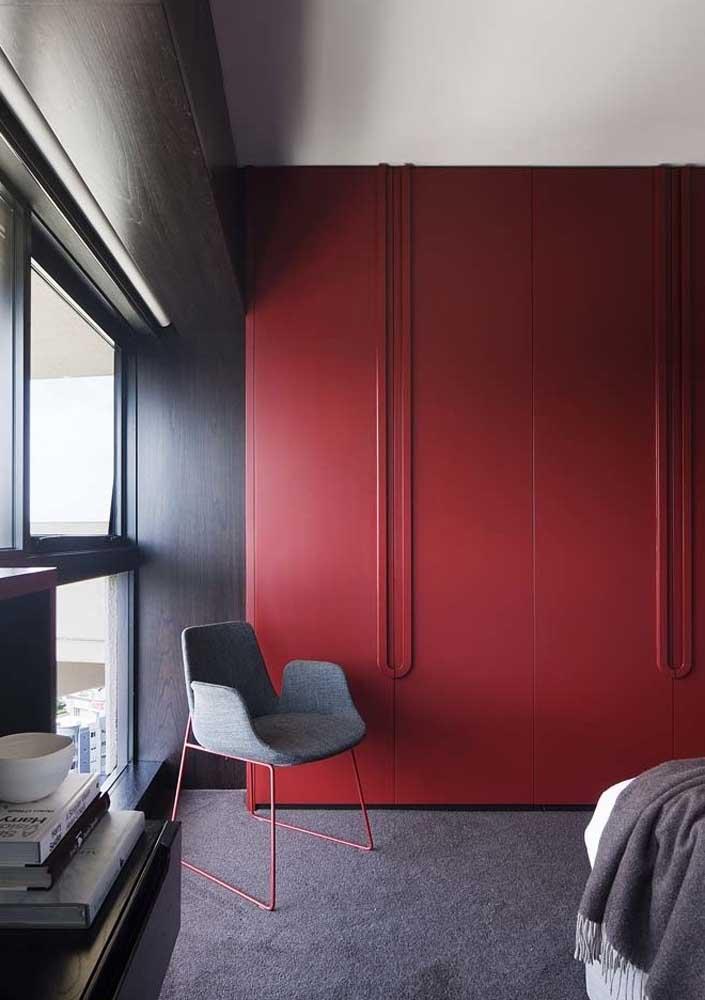 Para quebrar a seriedade do quarto cinza, você pode inserir um armário na cor vermelha.