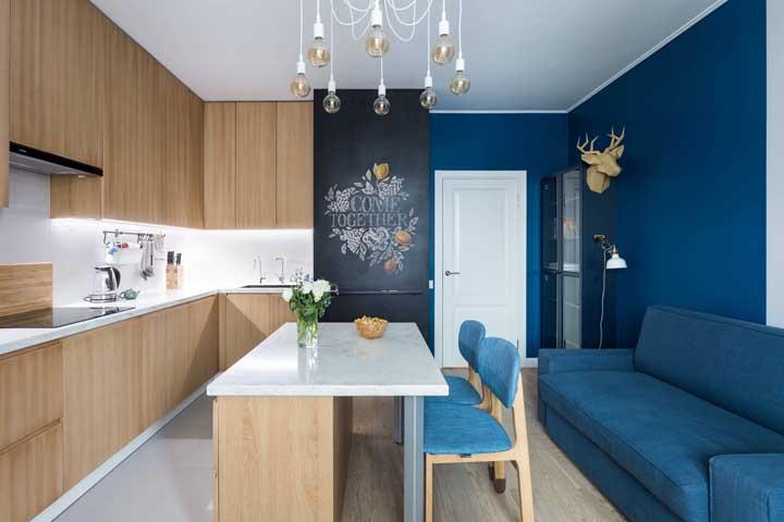Olha que combinação perfeita com a parede na cor azul de um lado, móveis de madeira no outro e um cantinho com a tinta lousa.