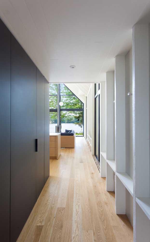 De um lado uma parede branca, do outro a parede preta e no meio o piso de madeira.