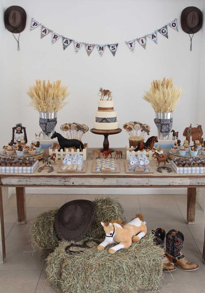 Uma mesa de madeira, botinha e chapéu de cowboy, cavalinho de pelúcia, entre outros itens são perfeitos para decorar a mesa de aniversário no estilo fazendinha.