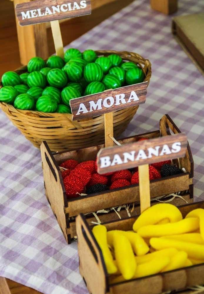 Compre frutas artificiais e coloque dentro de caixas de madeira para fazer a decoração fazendinha.