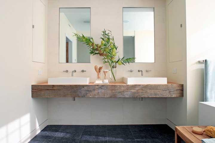 No banheiro, a madeira de demolição ganha mais charme na bancada da pia.