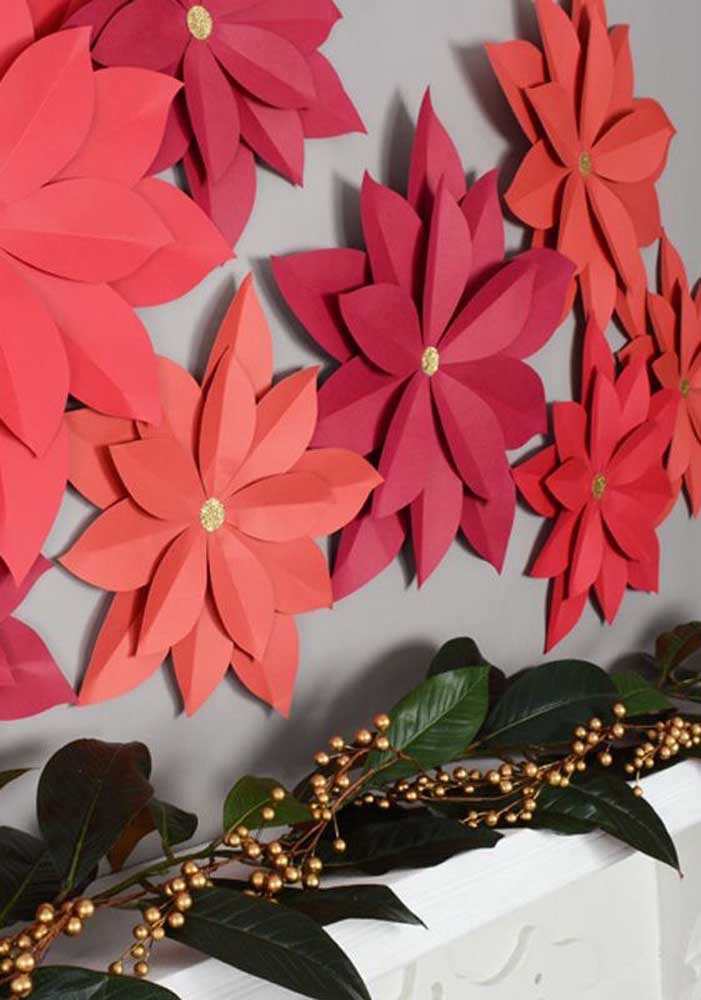 Você pode fazer um painel de natal escolar com flores grandes, já que são itens muito usados no natal.