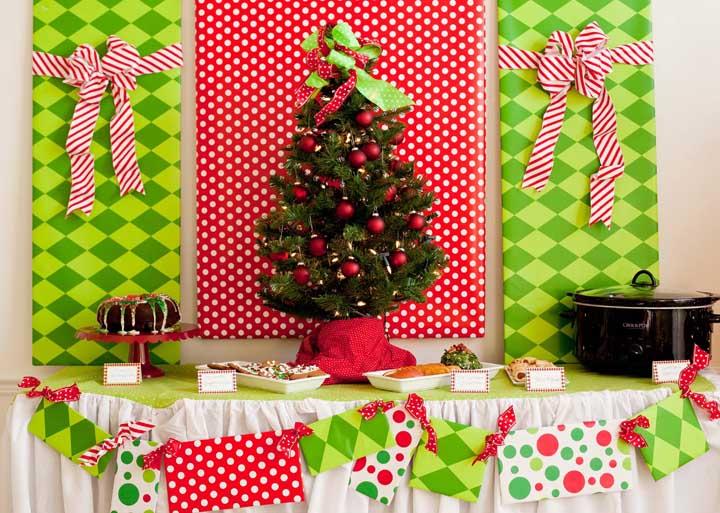 É possível usar tecidos ou papel de presente para formar um painel por trás da mesa com a árvore.