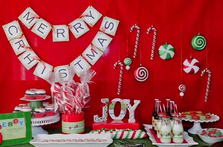 Pegue um tecido vermelho, coloque na parede, pendure alguns itens decorativos no tecido e fixe uma frase de natal.