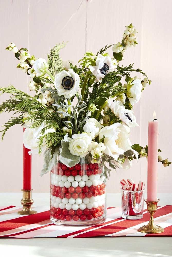 Pegue um pote de vidro, encha de bolinhas e complemente com flores.