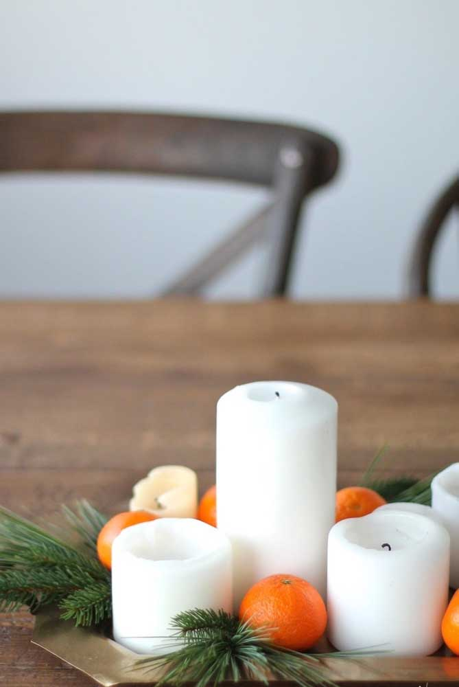 Para fazer um arranjo de natal mais natural, use velas, folhas e frutas.