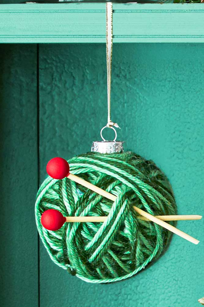 Você pode colocar outros enfeites na bola de natal artesanal.