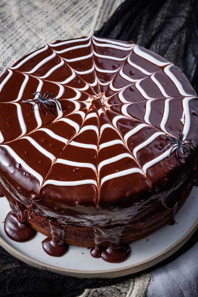 Faça uma calda de chocolate, espalhe em cima do bolo e desenhe várias teias de aranha.