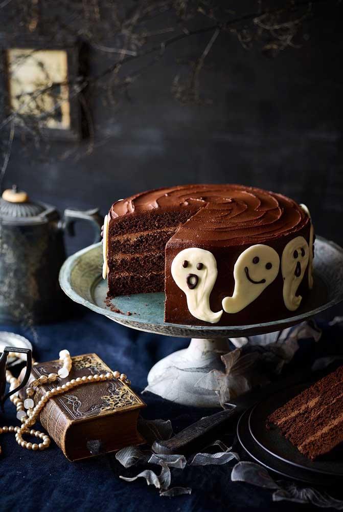 A decoração da mesa do bolo halloween ganha destaque com os elementos que fazem referência ao tema.