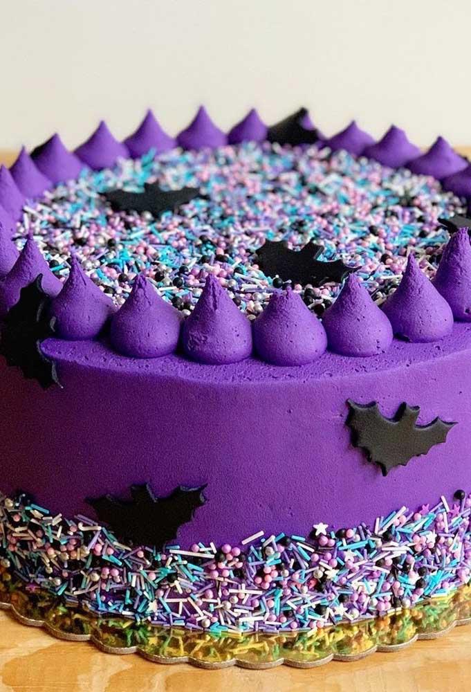 Prepare o bolo com a pasta americana na cor roxa e coloque enfeites coloridos no topo e lateral.