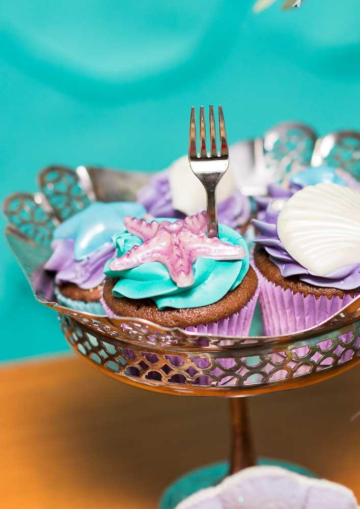 Cupcake decorado com chantilly e elementos que fazem parte do cenário sereia.