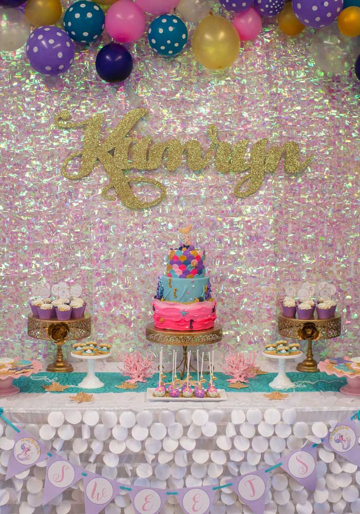 Quer fazer uma festa sereia com muito brilho? Basta caprichar no painel, enfeitar com balões coloridos e caprichar na mesa da festa.