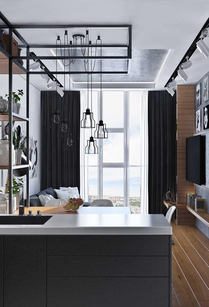Coloque luminárias pendentes para fazer a divisão da cozinha americana com sala pequena.