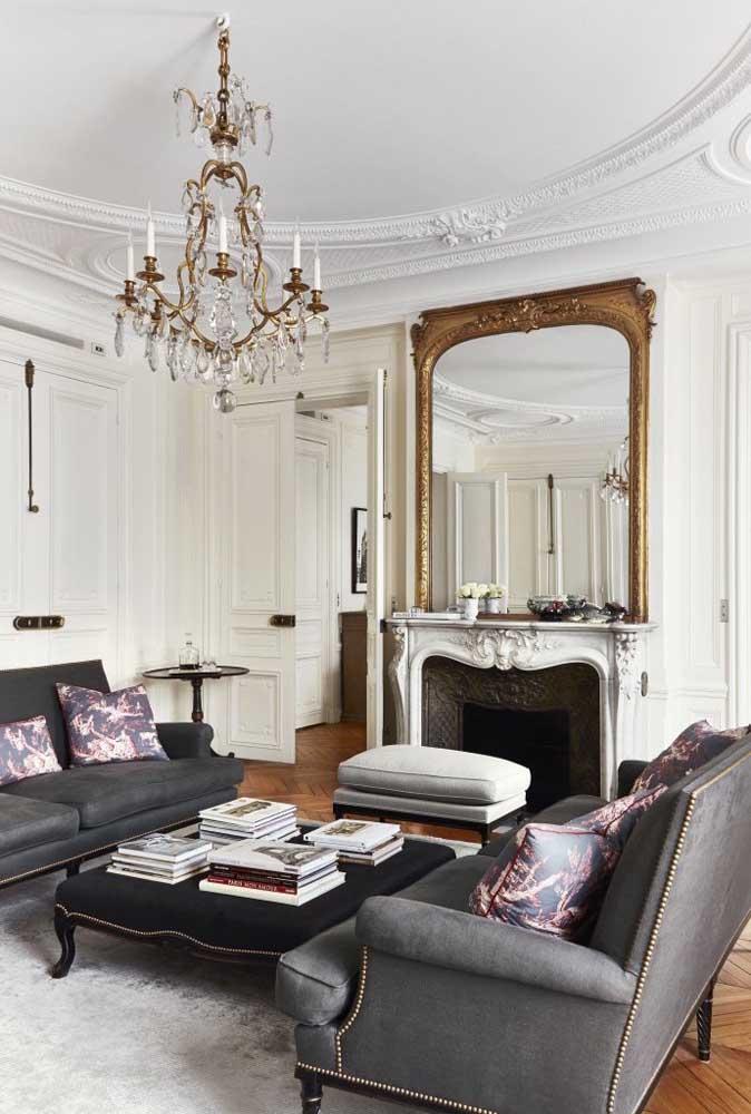 A sofisticação do lustre e da moldura do espelho destaca a sala de estar.