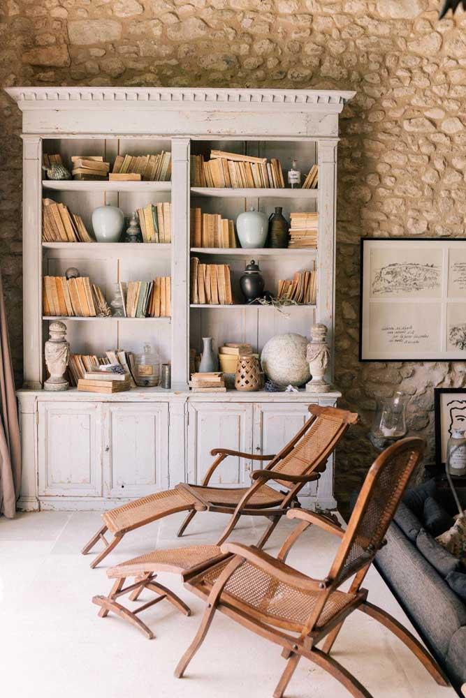 Uma estante de livro antiga, parede de pedra e cadeiras de madeira.