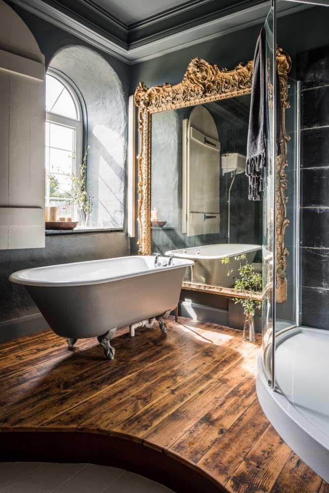 O luxo da moldura do espelho e o rústico do piso de madeira completam a decoração provençal desse banheiro.