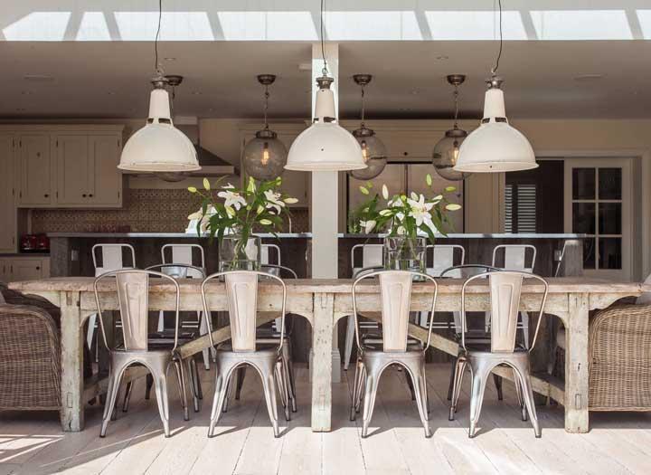 Que tal combinar a mesa de madeira antiga com cadeiras de plástico?