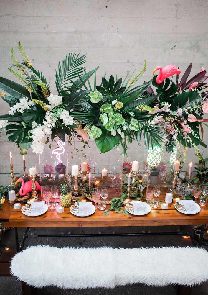 Faça uma decoração flamingo diferenciada com flores, folhas e velas.