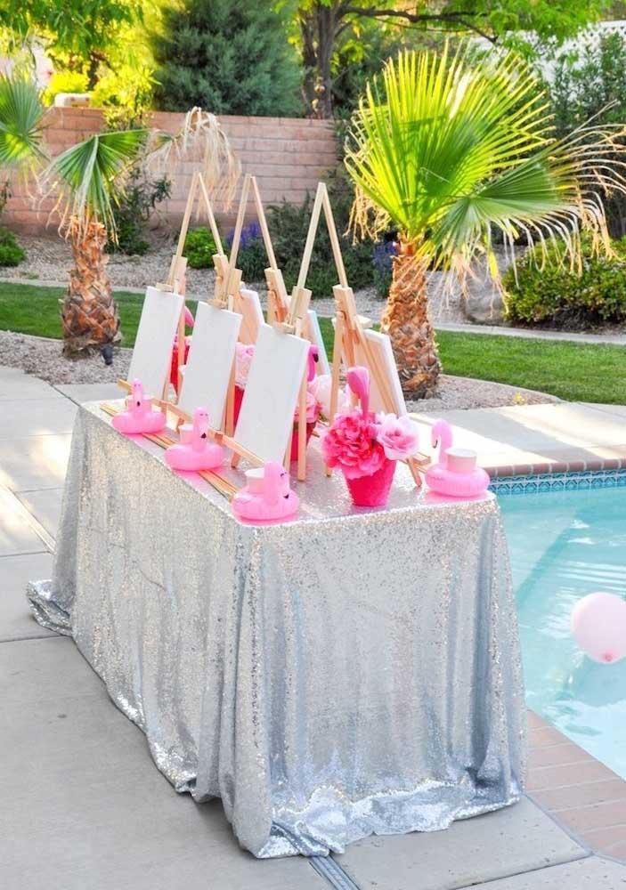 Mesa pronta para comemorar o aniversário com o tema flamingo na piscina.