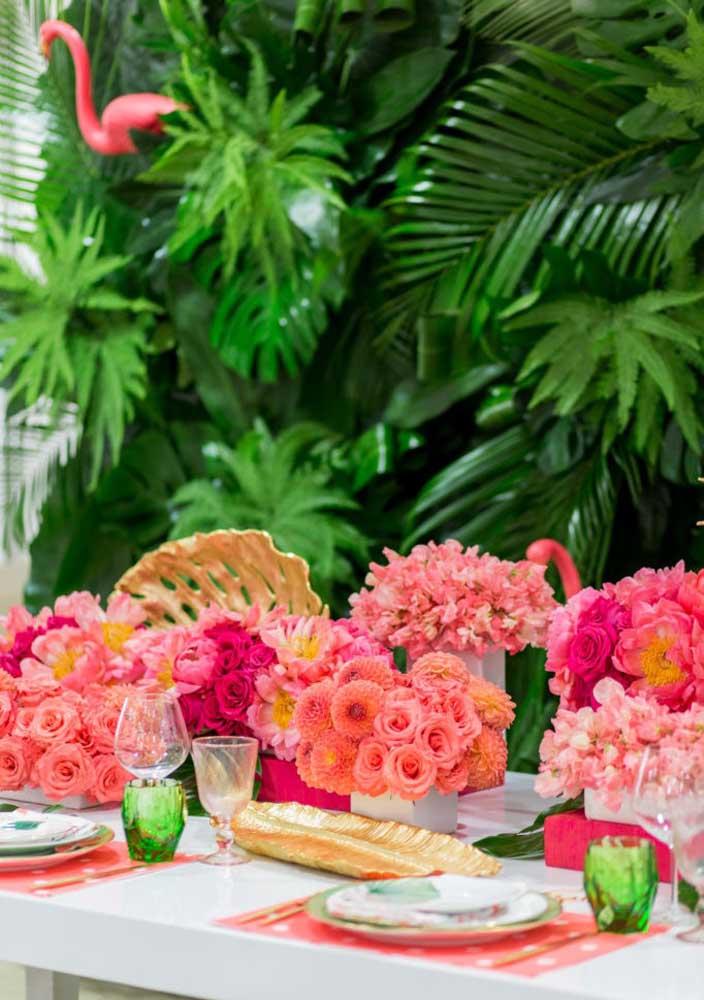 Decore a mesa principal da festa com arranjos de flores nos tons de rosa.