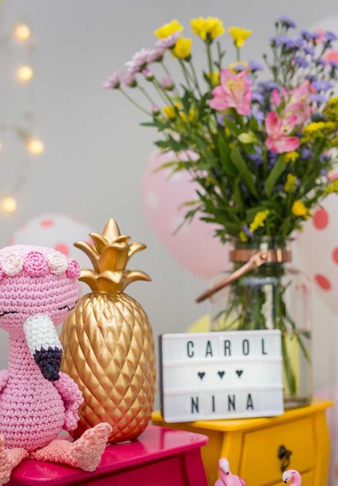 Flores, abacaxi e flamingo se complementam na decoração da festa.