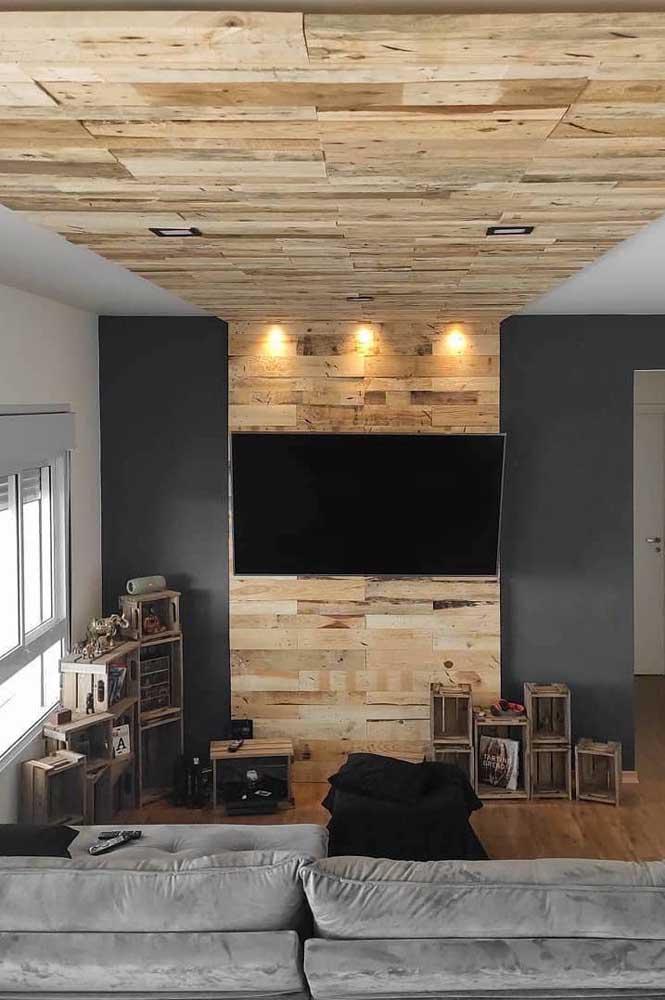 Um painel de pallet para TV que vai do teto até o chão.