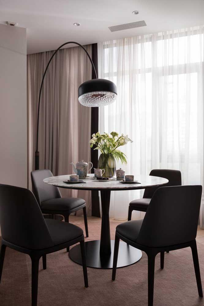 É possível escolher uma luminária de chão bem sofisticada para iluminar a mesa de jantar.